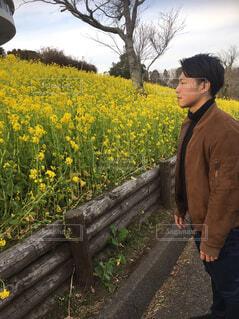 黄色の花の前に立っている男の写真・画像素材[1713281]