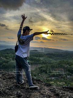 インドネシアの山から夕日に向かってなびく男の写真・画像素材[1715893]