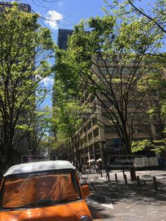 青空の下 新緑の中 遊歩道のオレンジ色の車とイスとテーブルの写真・画像素材[2037150]