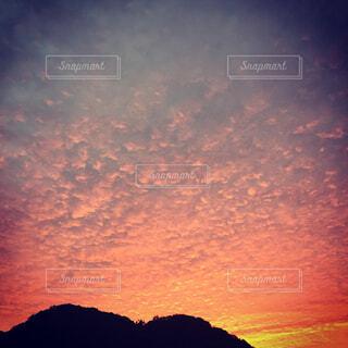 背景の山、沈む夕日、うろこ雲の写真・画像素材[1721388]