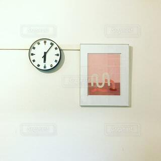 壁に掛かっている時計とピンクの絵の写真・画像素材[1730769]