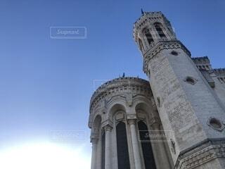 建物の側に時計と大きな背の高い塔の写真・画像素材[1731821]