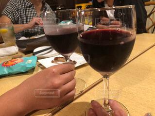 ワイングラスを持つテーブルに座っている女性の写真・画像素材[1734829]