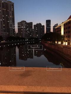 バック グラウンドで市と水の体の上の橋の写真・画像素材[1736033]